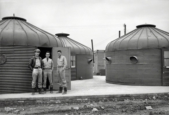 Three U.S. pilots stand in front of a cluster of Dymaxion Deployment Unites, NOrth Africa, 1944